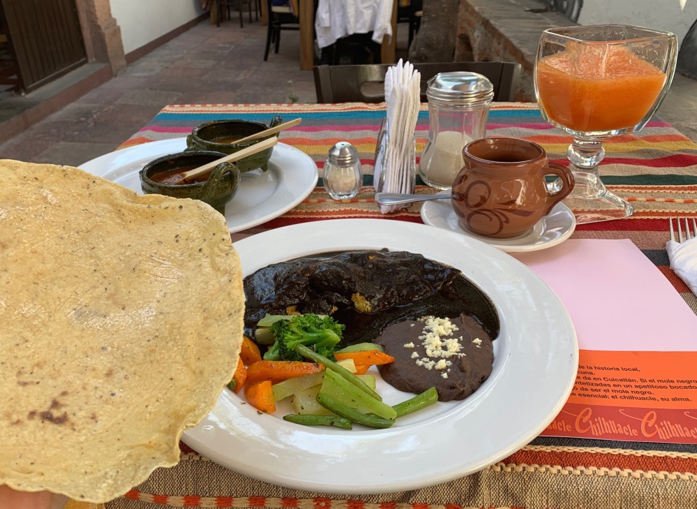 Omelet with mole sauce, vegetables, refried beans, tortillas, a side of two salsas, coffee, and papaya juice