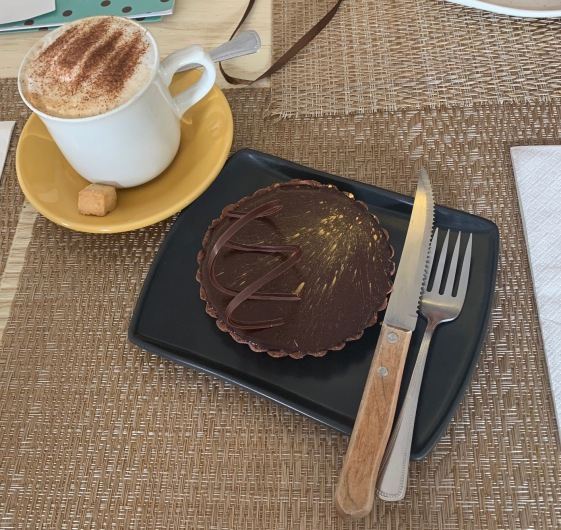 Gold-dusted chocolate tart with a cappuccino at Moshi Reposteria