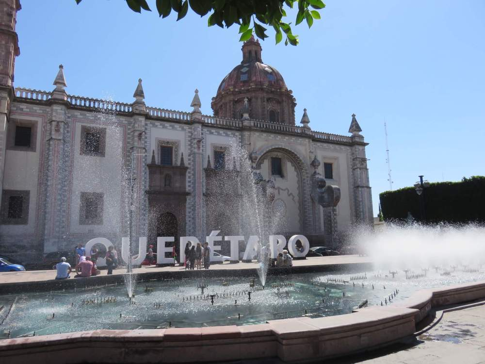 Musical fountain, city sign spelled in big block letters, and Santa Rosa de Viterbo church in the Plaza Mariano de las Casas