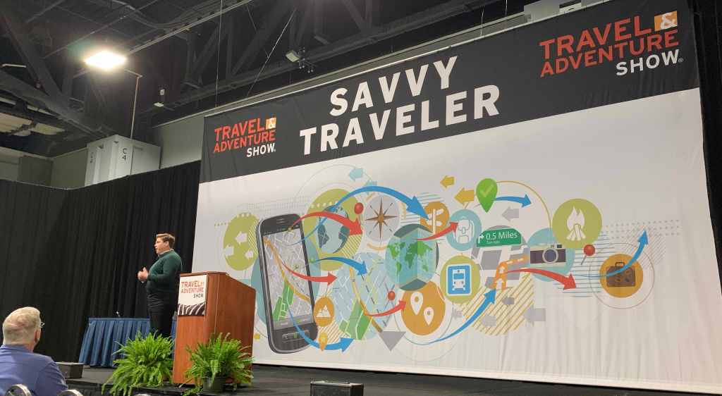 Angel Castellanos speaking about travel apps, tips, and resources on the Savvy Traveler stage at the DC Travel & Adventure Show