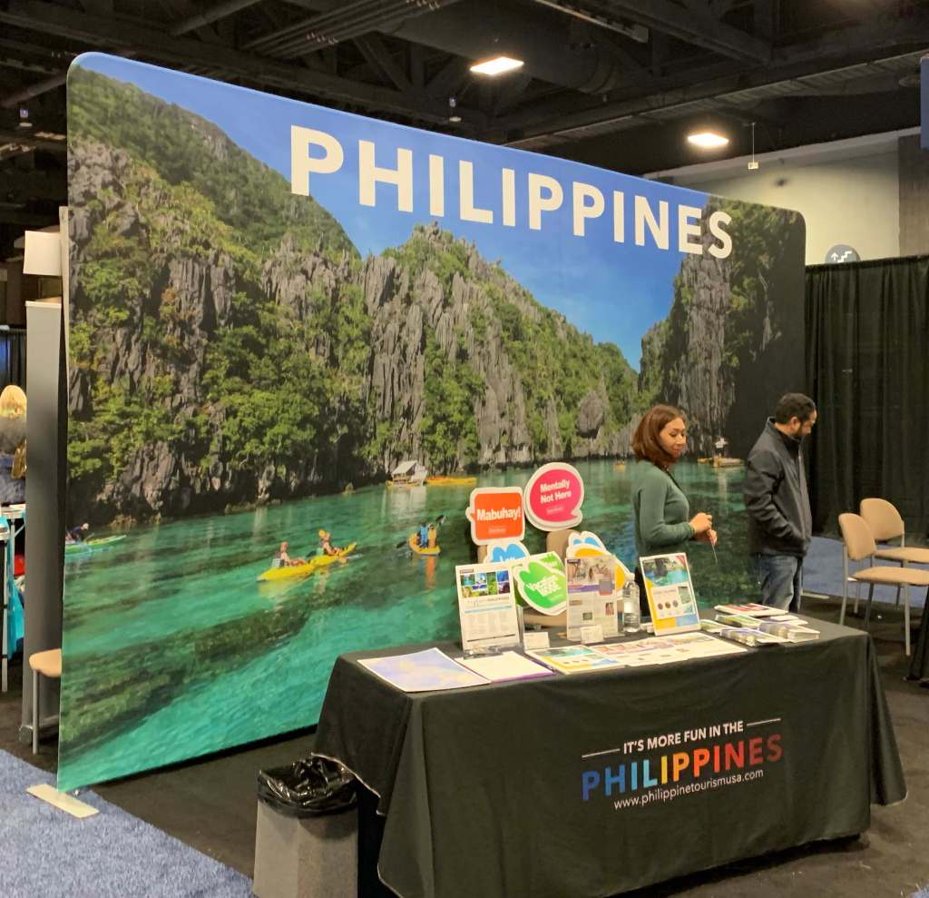 Philippines exhibit booth with poster backdrop of beautiful lake surrounded by stunning rocks