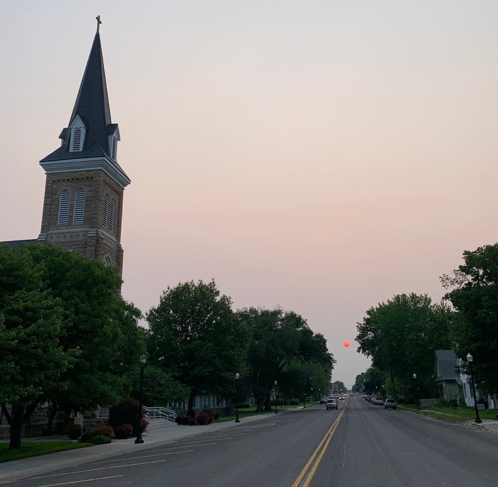 Bertrand Avenue in Saint Marys, Kansas near sunset, showing a bright pink sun due to haze and fires from Canada. The Immaculate Conception Church is on the south side of the road.