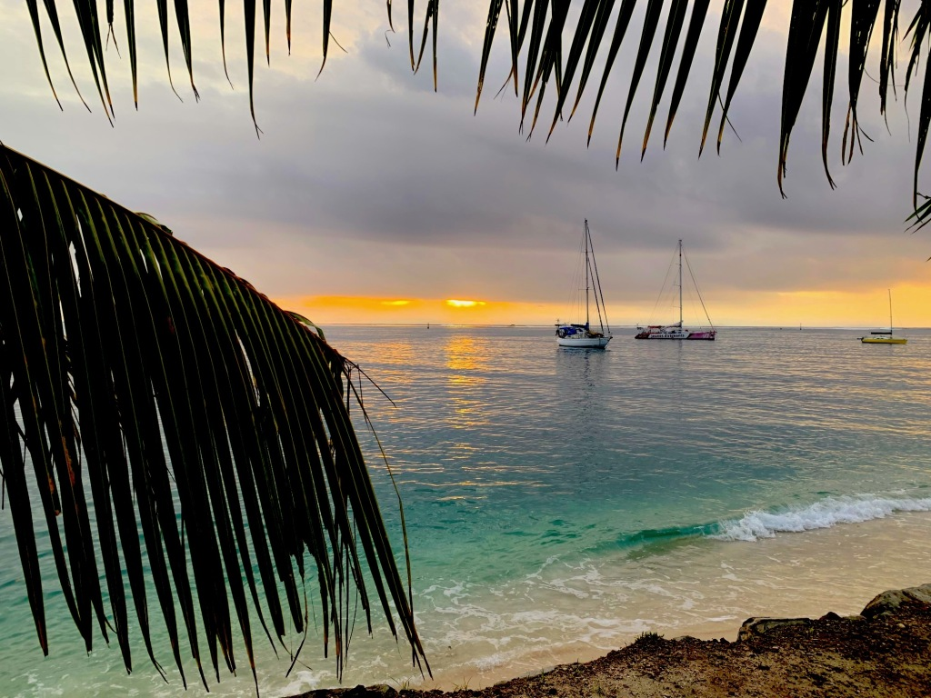 Sunset with palm trees and boats, from the Huahine Yacht Club in Fare.