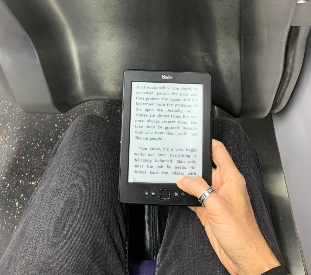 Photo of my hand holding a Kindle...reading on the Metro commute