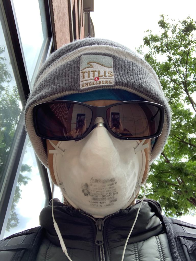 Early May selfie in a facemask, sunglasses, winter hat, and earphones on my way to the grocery store