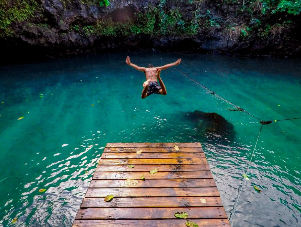A man jumps into the To-Sua Ocean Trench, a swimming hole in Samoa