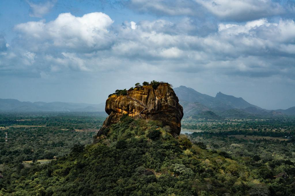 View of Sigiriya rock and surrounding countryside, with mountains in the back