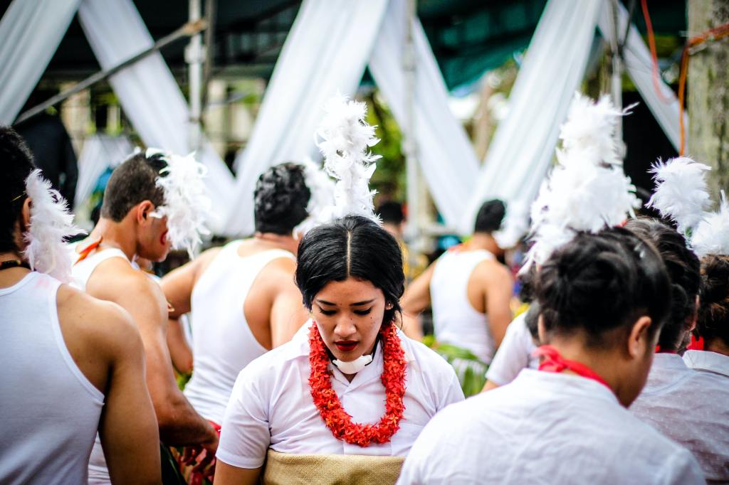 A group of people dressed in traditional adornments of white feathers and shirts, with one woman looking down pensively while everyone else has their backs turned