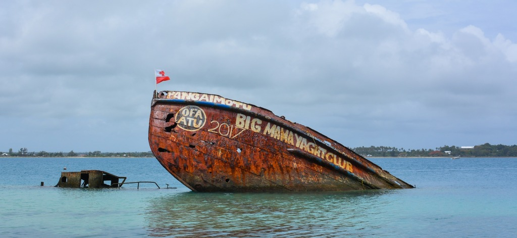 "Partially sunken ship in the water on Pangaimotu Island. The side of the ship reads ""Big Mama Yacht Club"" and ""Ofu Atu 201"" and there is a small flag of Tonga on the ""mast."""